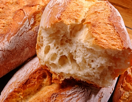Freshly baked crisp crusty white bread broken open to display the light airy centre of the loaf or roll Stock Photo - 15471746