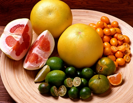 Variety of citrus fruits arranged on a plate with grapefruit, lemon, limes, clementine, naartjie, orange and small kumquats each sliced to display the interior pulp