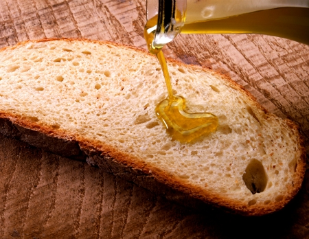 newly baked: Fresh golden olive oil being poured and drizzled onto a slice of newly baked unbuttered bread Stock Photo