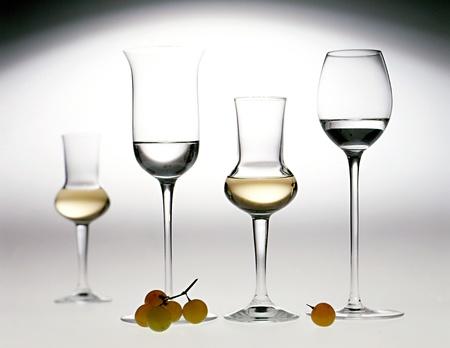 Gafas elegantes en diferentes formas de grappa, un aguardiente de orujo de oliva italiano, con destilado incoloro y de color tanto a la ligera