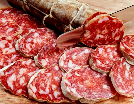 cured: Sliced fresh salami, a traditional dried and cured Italian sausage prepared from meat such as pork or beef mixed with seasoning, spices and fat