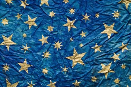 Blu fondo con estrellas doradas sobre un papel arrugado Foto de archivo