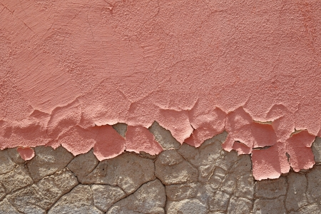 Architectural background of friable peeling pink paint on a damaged cracked wall exposed to weathering photo