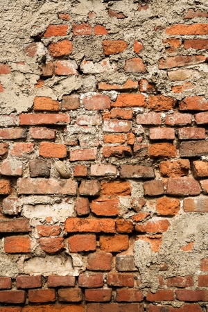 Abstract background texture of an old crumbling brick wall with damaged bricks and peeling plaster Stock Photo - 16185568
