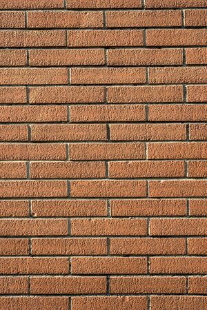 Abstract background with a neat rough textured face brick wall with rectanguler orangey red bricks in rows Stock Photo - 16185578