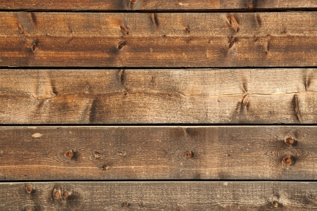 Architectural background of parallel horizontal knotty timber boards with a rough textured surface and woodgrain detail