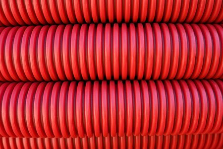Abstract bckground of rolled red plastic electrical conduit for use in underground cable installation