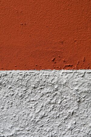 smoother: Abstract background of a bicolour painted wall with differing colours, red and grey, and textures, rough below and smoother above