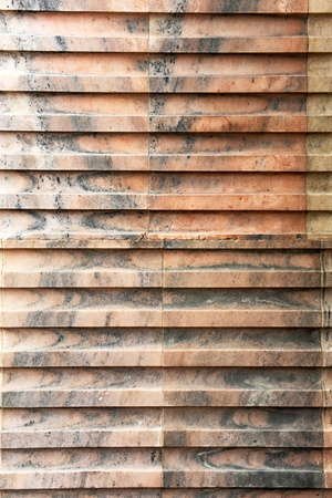 mottling: Abstract background pattern of a pink marble wall with marbled mottling and carved ridges and indents