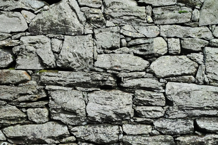 drystone: Abstract background of a dry-stone wall construction using irregular natural rough stones which are interlocked by their shape without using mortar Stock Photo