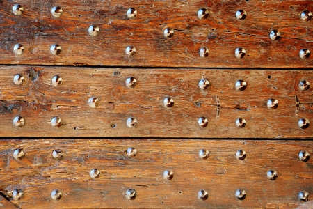 Abstract background of an old studded wooden door detail with multiple decorative studs in a repeat pattern on a woodgrain surface