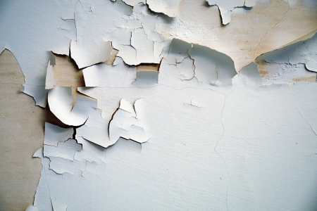 Abstract background texture of flaking cracked paint peeling off a cement wall Stock Photo