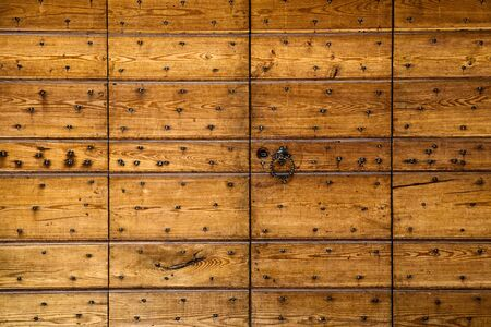 differing: Abstract background of wooden panels studded with nails of differing sizes in rows with woodgrain texture