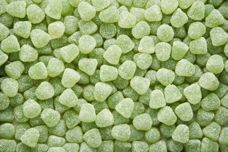 sugarcoated: Background of a pile of random green sugar-coated pastilles or sweets for children