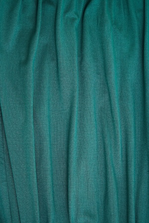bluey: Abstract background texture of a length of bluey green hanging rough textured woven textile falling in folds, Stock Photo
