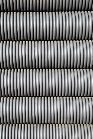 conduit: Background texture and pattern of ridged grey plastic electrical conduit or tubing coiled one on top of each other