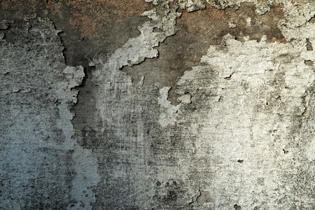 Abstract background texture of a dirty, stained grungy wall with damaged peeling plaster