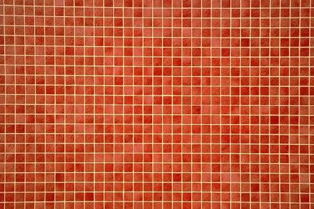 Fondo arquitect�nico de un muro cubierto de coloridos azulejos de mosaico anaranjado-rojo en un patr�n de repetici�n de filas