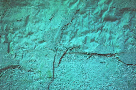 Abstract background texture of a damaged painted turquoise wall with cracked and missing plaster that has been painted over to try and conceal the damage photo