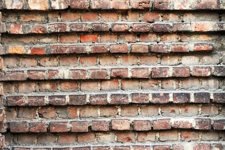 Abstract architectural background texture and pattern of an old grunge wall withalternating rows of indented and raised red bricks Stock Photo - 17302184