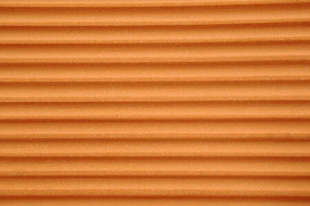 fluted: Abstract background of a fluted stone wall with horizontal gullies and ridges in a caramel brown colour with a smooth speckled surface