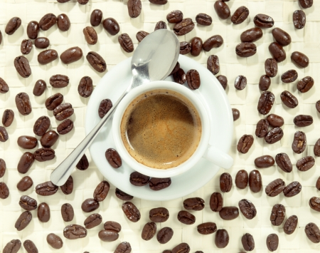 foamy: Cup of foamy coffee on plate with spoon surrounded by coffee beans, high angle Stock Photo