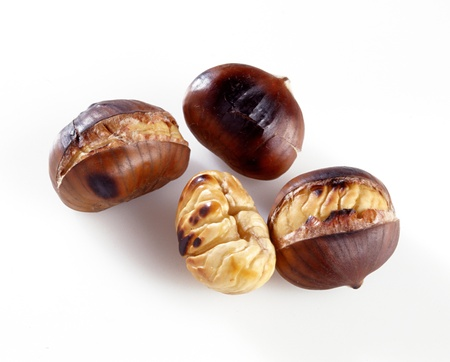 A group of roasted chestnuts showing one peeled kernel , two that have split open with the heat and one wirh a whole husk over white Stock Photo