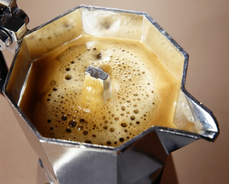 Closeup high angle view of frothy freshly percolated espresso coffee in a stovetop moka espresso pot