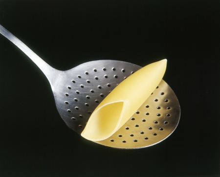 the draining: Single pasta tube on a stainless steel colander or draining spoon on a dark studio background
