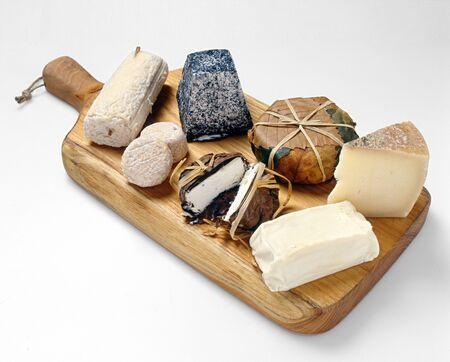 Tabla de madera con un surtido de quesos gourmet que contiene porciones de queso blandos y duros Foto de archivo