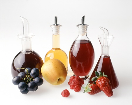 Elegantly shaped clear glass bottles containing four different fruit vinegars with a the corresponding fresh fruit in the foregorund on a white background
