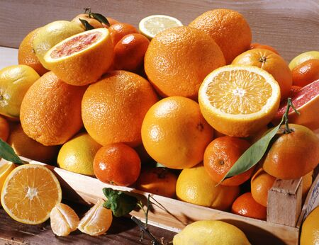 Wooden box of fresh whole and halved oranges with a variety of other citrus fruits including clementine and mandarin Stock Photo - 17562101
