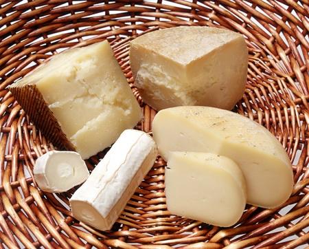 Surtido de quesos italianos se muestran en una cesta con dos quesos duros y un queso suave cada rodajas para mostrar la textura