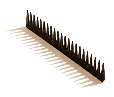 toothed: Black toothed hair comb photographed balancing upright with the teeth in the air casting a shadow on a white background