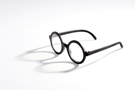 Vintage spectacles with round lenses on a white background casting an interesting shadow with copyspace photo