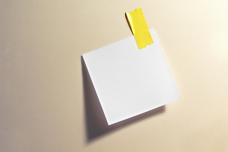 notelet: Blank white square note stuck up with a small piece of yellow tape on a neutral coloured board for your memo, message or reminder
