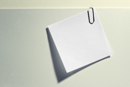 notelet: Small white blank notelet attached to a larger light grey document with a paperclip for your memo, reminder or addendum