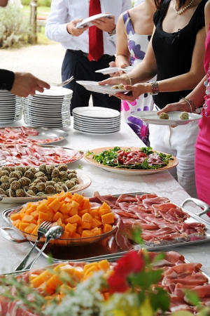 Food display with an array of cold meat, salad and vegetable dishes at a banquet or buffet with people standing in line being served Stok Fotoğraf