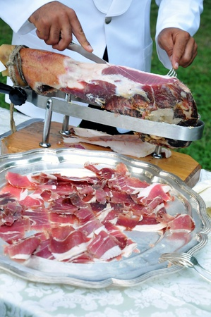 banqueting: View of the hands of a male chef carving a side of cold cured ham into thin slices arranged on a platter in the foreground for a catered event or buffet Stock Photo