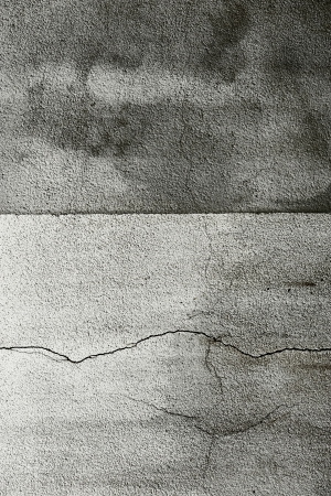stippled: Cracked grungy cement wall background with a stippled rough surface and a central division line between a lighter and darker grey colour Stock Photo