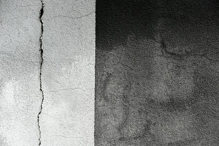 stippled: Background texture of a cracked grunge cement wall divided vertically into a light and darker grey section with a rough stippled surface