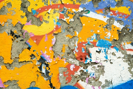 Colourful remnants of peeling graffiti with the paint peeling off the surface of the cement wall in a background texture and pattern photo