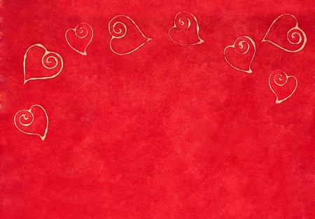 curlicue: Romantic delicate curlicue hearts forming a border on a textured red background with copyspace for your Valentines, wedding or anniversary greeting