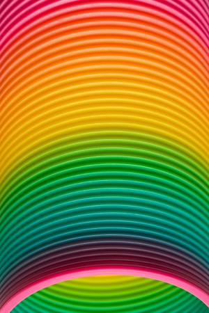 Closeup of the graduated rainbow colours of a vintage spiral coiled plastic slinky toy in the form of a spring photo