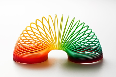 Rainbow coloured slinky toy made of a plastic wire spiral coil which enables flexibility and mobility photo