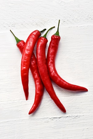 flavouring: Bunch of colourful red hot chili peppers or capsicum used as a pungent flavouring and spice in cooking or dried to produce cayenne pepper