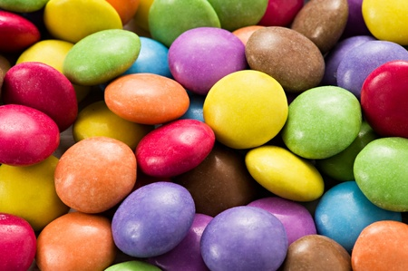 sugarcoated: Background of colourful sugar-coated chocolate smarties in the colours of the rainbow or spectrum Stock Photo