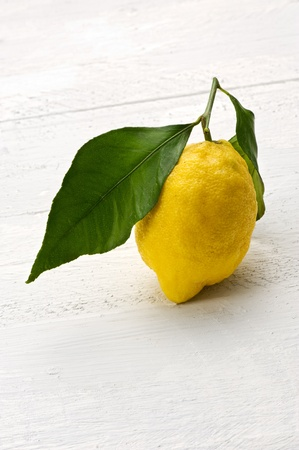 flavouring: Single fresh yellow lemon with a stalk and leaf with its sour tangy taste and high in vitamin c it is used as a flavouring, cooking ingredient and garnish Stock Photo