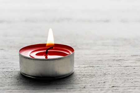 Close up of a single burning red tealight candle in a metal base on a white textured background with copyspace for your message or invitation