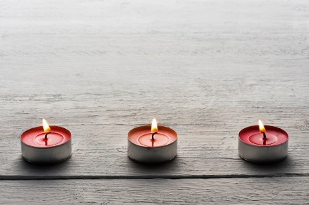 Row of burning red tealights or small candles on a dark wooden surface with copyspace above